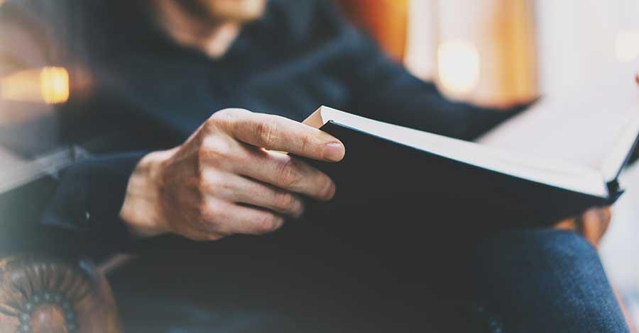 Bild zeigt einen Mann mit eionem Buch in den Händen