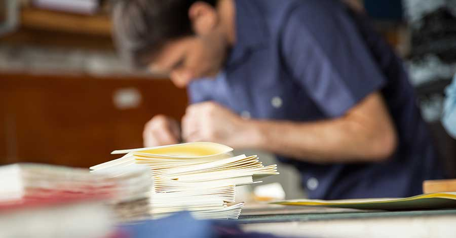 Bild zeigt Buchbinder bei der Arbeit in Buchbinderei
