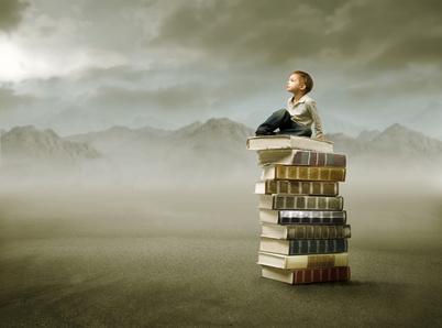 Kind sitzt auf Büchern