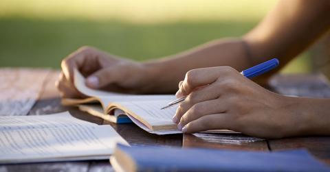 Bild zeigt Student mit Büchern beim Lernen
